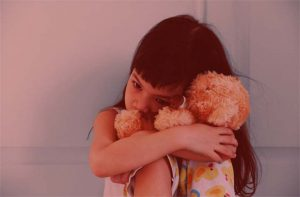 Asian girl hug her doll and cry or scare or sad or feel bad  or in trouble.Sitting on the bed.Selective focus.Concept of orphan kid.; Shutterstock ID 694035802; PO Number - Raise a BBC PO Using Vendor No. 1150465: -; Employee Email: -